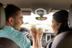 couple driving car with coffee